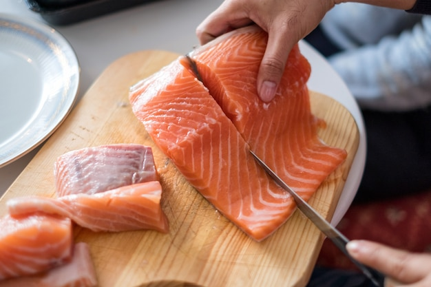 Hand chef using knife slice raw salmon on chopping board