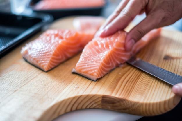 Ручной повар с ножом нарезал сырого лосося на разделочной доске