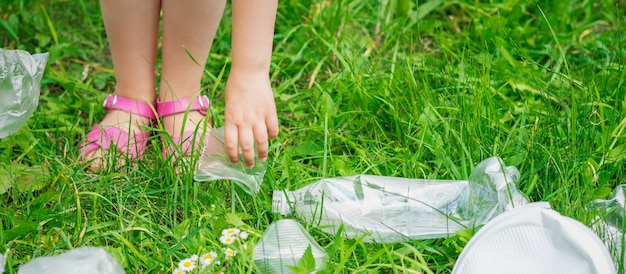 Hand of child cleans green grass from plastic trash in the park