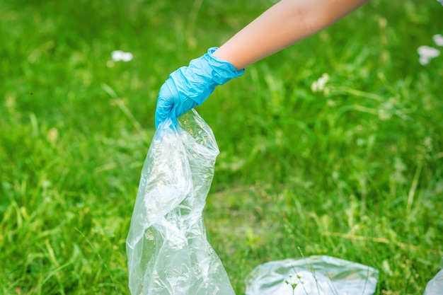 Hand of child cleans the park from plastic debris lying on the green grass