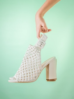 The hand of the child holds fashion summer shoes on a green