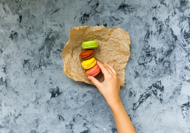 Hand child taking tasty colorful macaroons from table