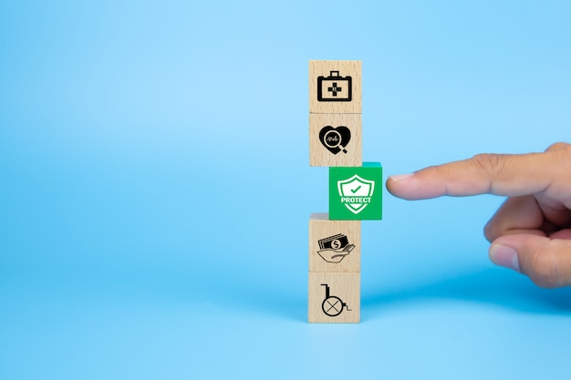 Hand choose a cube wooden toy blocks with protect icon for safety family and health insurance concepts.