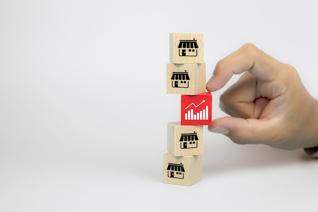 Hand choose graph icon with franchise marketing icons store on cube wooden toy blog is stacked for business growth and branch expansion strategy of financial.