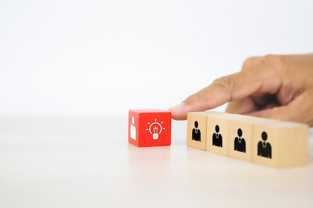 Hand choose human with light bulb icon on cube wooden block stack.