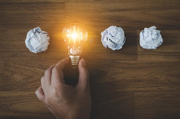 Рука выбирает лампочку и мятую офисную бумагу