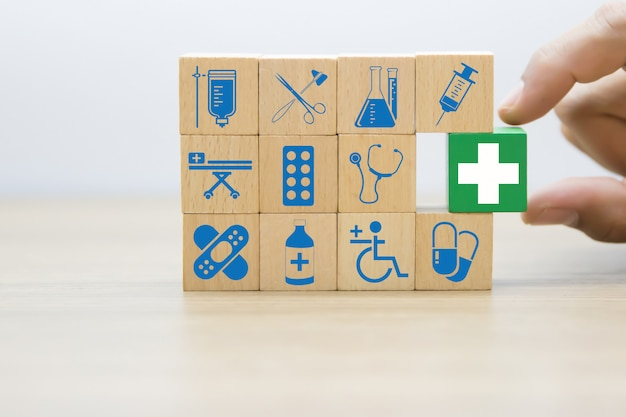 Hand choose medical and health icons on wooden blocks.