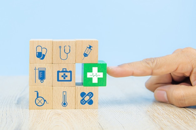 Hand choose medical icon on cube wooden toy blocks stack in with other medical symbols.