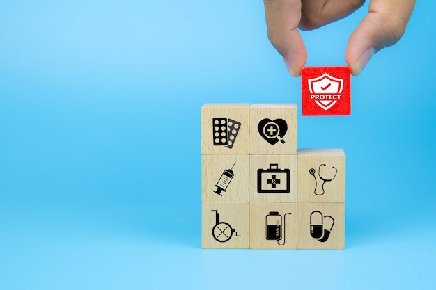 Hand choose medical icon on cube wooden toy blocks stack in with other medical symbols