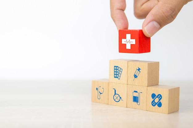 手は木製のブロックに心臓波信号アイコンと医療シンボルを選択します。
