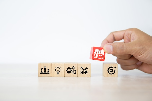 Hand choose wooden blocks stacked with franchise business store icon.