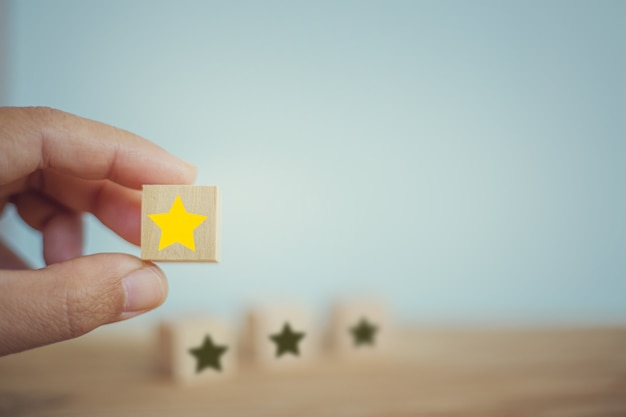 Hand chooses wooden yellow star shape on table