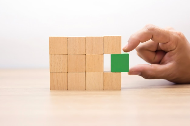 Hand choosing green color wooden block with out graphic.