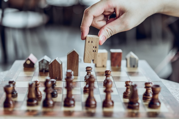 Hand choosing mini wood house model from chess game, choose what's the best.