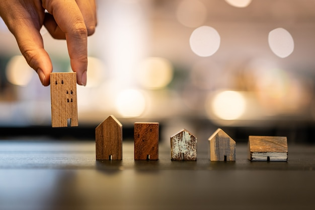 Hand choosing mini wood house model from mode on wood table