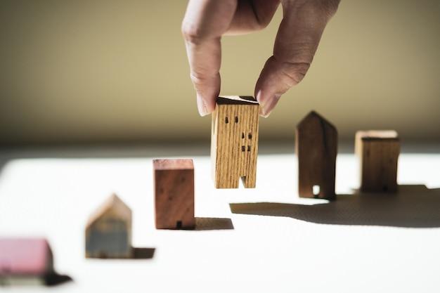 Hand choosing mini wood house model from model, selective focus,