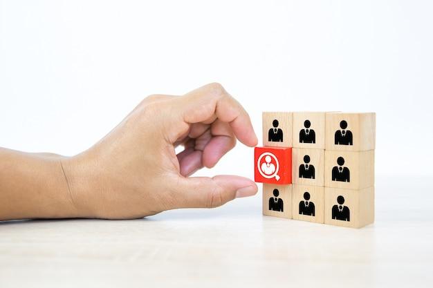 Рука, выбирая значок людей на кубиках деревянных игрушечных блоков, сложенных.