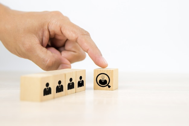 Hand choosing people icons head with a light bulb on cube wooden toy blocks.