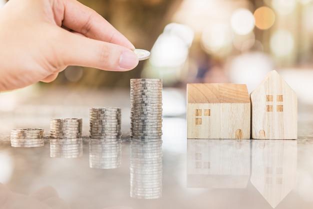 Рука выбирая ряд денег монетки на деревянном столе и мини деревянном доме,