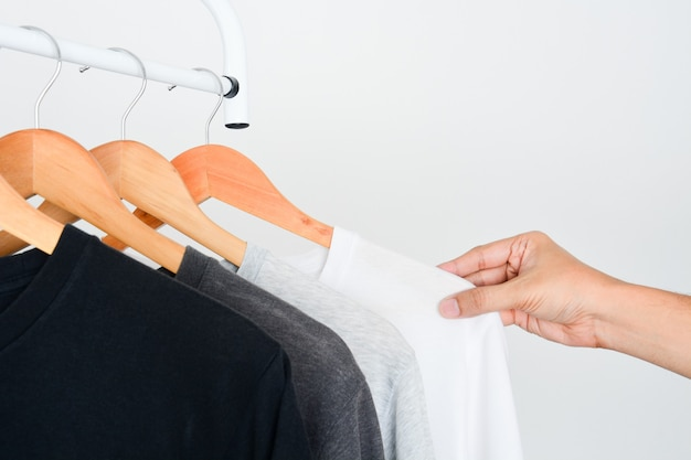 Рука выбирает футболку белого цвета из коллекции футболка, висящая на деревянной вешалке для одежды