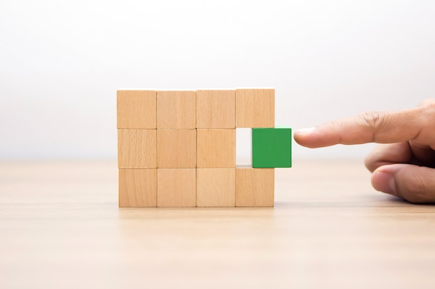 Hand choosing wooden block with out graphic.