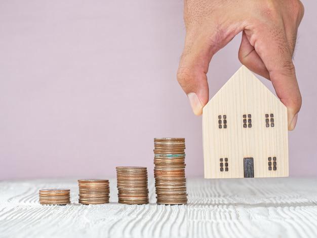 Рука, выбирая модель деревянного дома и монету стека на белый деревянный стол, выборочный фокус. планирует купить недвижимость. выбери лучшее