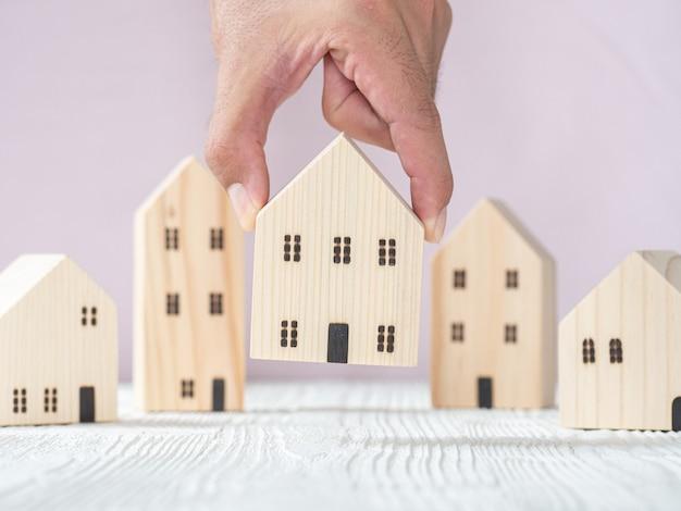 Рука, выбирая модель деревянного дома из ряда модели на белом деревянном столе, выборочный фокус. планирует купить недвижимость. выбери лучшее