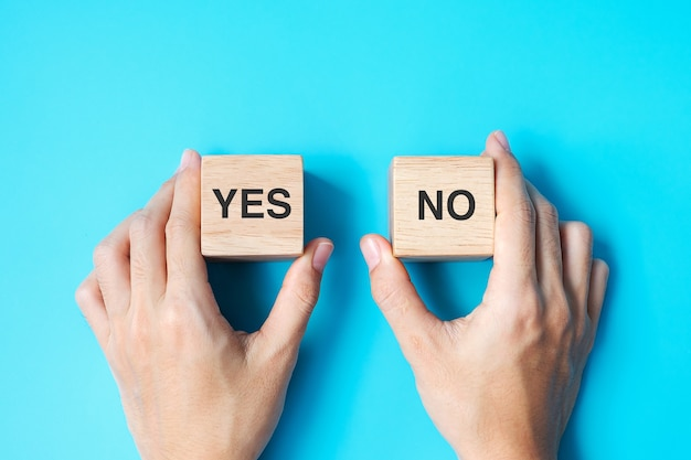 Hand choosing yes or no block. answer, question and decision concept