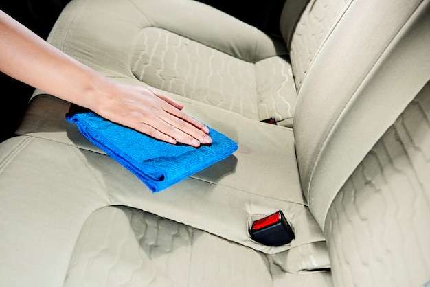 Hand cleaning car interior with rag cloth