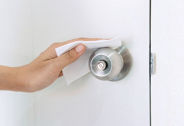 Hand cleaning door lock with disinfectant wet wipe. concept of disinfecting surfaces from bacteria or viruses. close up