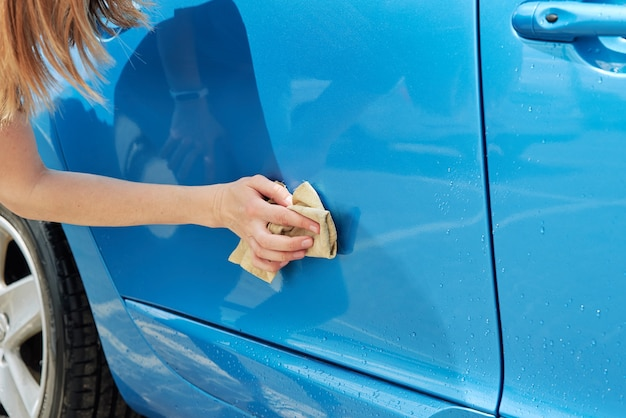 Hand cleaning modern blue car with microfiber cloth