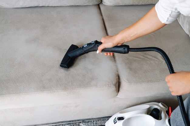 Hand cleaning a sofa with a steam cleaner