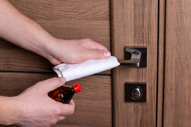 Ручная чистка деревянной двери. алкогольное лечение. коронавирус
