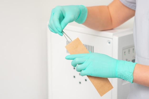 손은 공예 가방에 넣은 핀셋을 청소합니다. 초음파 세척기.