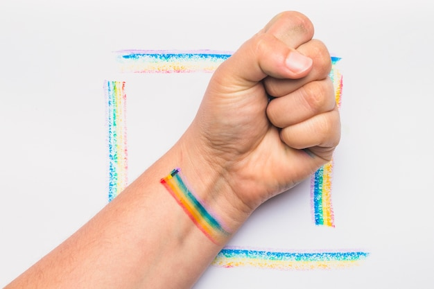 Hand clenched into fist with stripes in lgbt colors