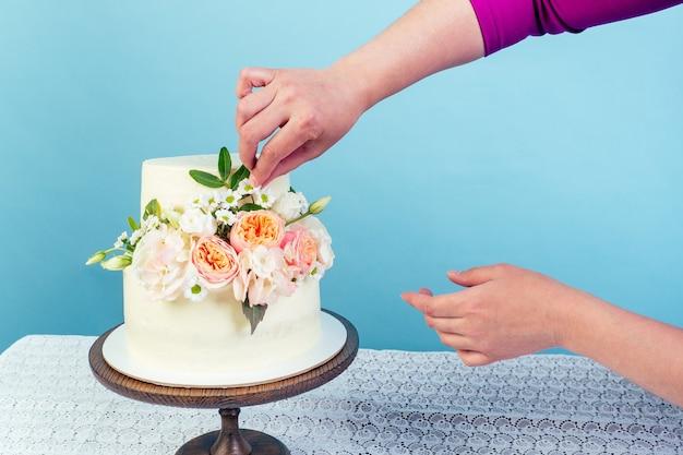 Рука крупным планом украшает рабочее пространство пекарь кондитер кондитер аппетитный кремовый белый двухъярусный свадебный торт, украшенный живыми цветами на столе студии на синем фоне