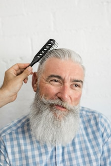 Hand combing old man gray hair