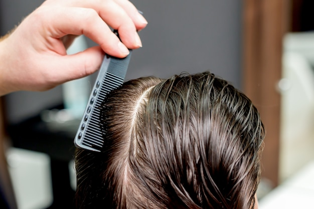 Hand combs hair of woman close up