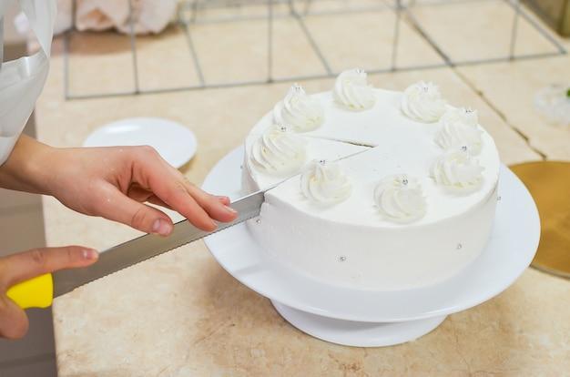 手菓子専門の製菓用ナイフが美しい白いケーキを切る