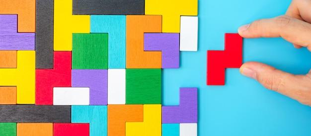 파란색 배경, 기하학적 모양 블록에 다채로운 나무 퍼즐 조각을 손으로 연결합니다. 논리적 사고, 수수께끼, 솔루션, 합리적, 전략, 세계 논리의 날 및 교육의 개념