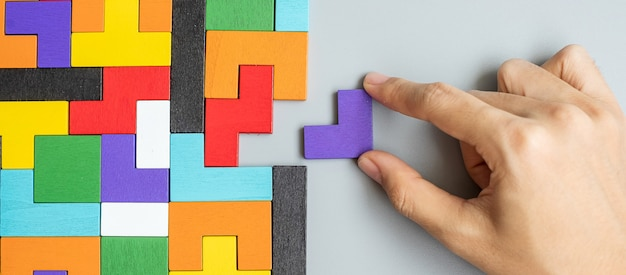 Hand connecting geometric shape block with colorful wood puzzle pieces.