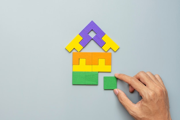 Hand connecting home shape block with colorful wood puzzle pieces on gray . logical thinking, business logic, solutions, rational, house, real estate and strategy concepts