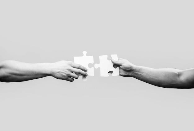 ジグソーパズルを接続する手。ビジネスソリューション、成功と戦略の概念。黒と白。