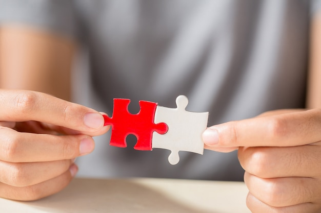 Hand connecting two puzzle pieces on table background