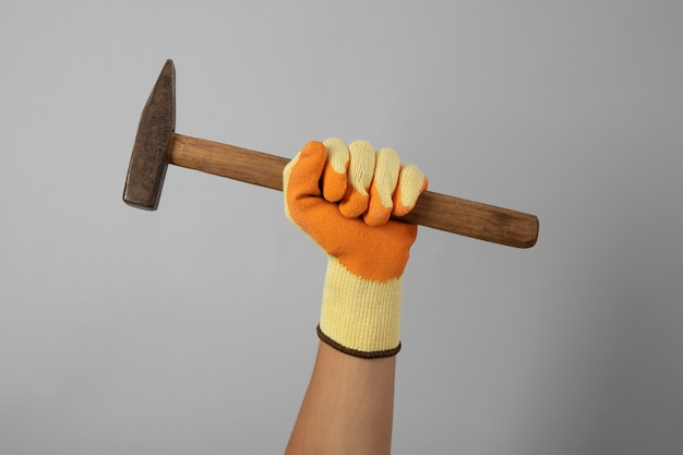 Hand in construction glove hold hammer on gray