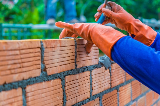 Hand of construction worker laying down brick wall one by one using mortar to join