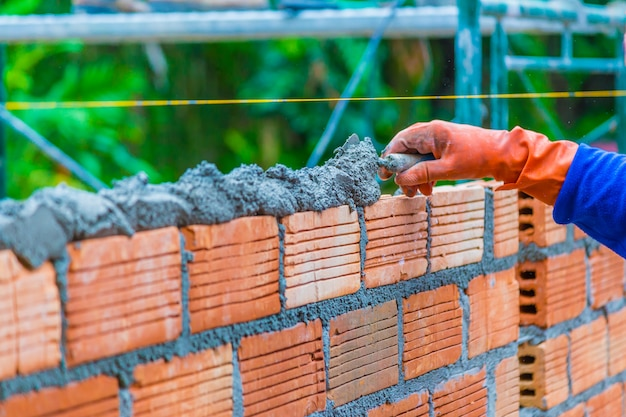 Hand of construction worker putting down mortar paste on top of unfinished brick wall