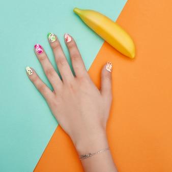 手の化粧品の爪の色とケア、プロのマニキュアとケア製品。色紙の背景の上に横たわる手