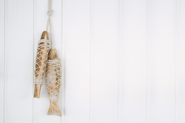 Hand crafted fish wood on white wooden background with copy space