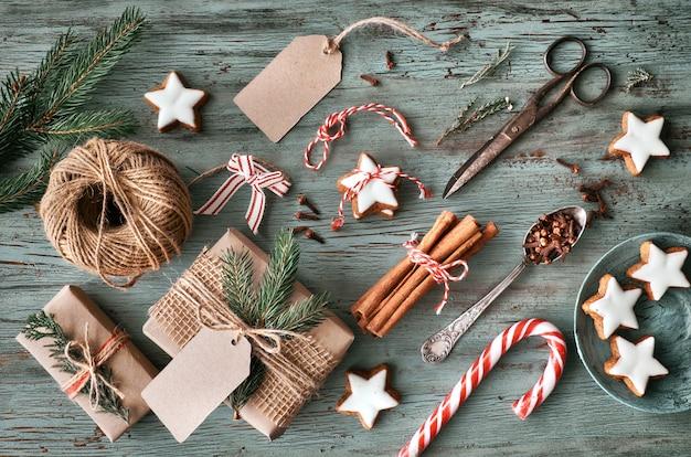 Подарки ручной работы на темном деревенском деревянном столе с рождественскими украшениями
